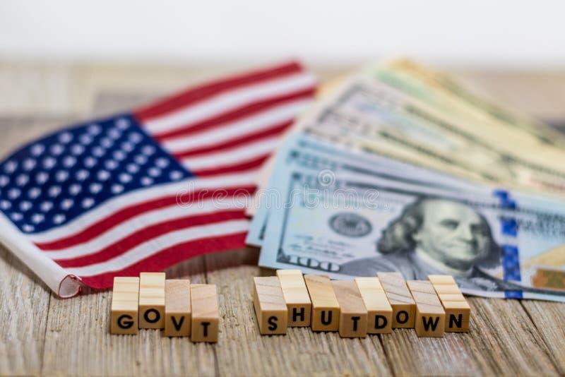 Het concept van de V.S. van de overheidssluiting met Amerikaanse vlag en geldrekeningen op witte achtergrond en houten raad royalty-vrije stock afbeeldingen