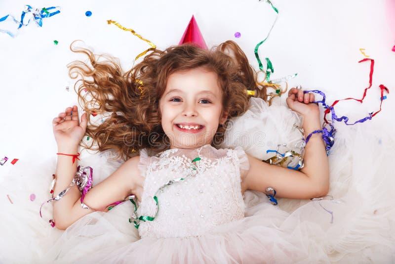 Het concept van de vakantie Weinig grappig meisje die in multicolored confettien op verjaardagspartij liggen stock foto's