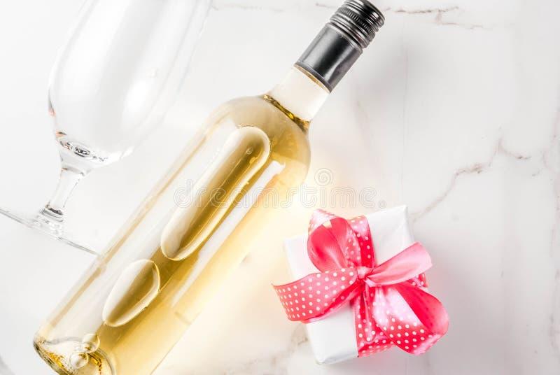 Het concept van de valentijnskaartendag met wijn, twee glazen en giftdoos op wh stock foto's