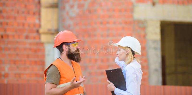 Het concept van de veiligheidsinspecteur De inspectie van de bouwwerfveiligheid Bespreek vooruitgangsproject Vrouweninspecteur en stock foto