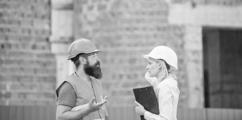 Het concept van de veiligheidsinspecteur De inspectie van de bouwwerfveiligheid Bespreek vooruitgangsproject Vrouweninspecteur en stock afbeelding