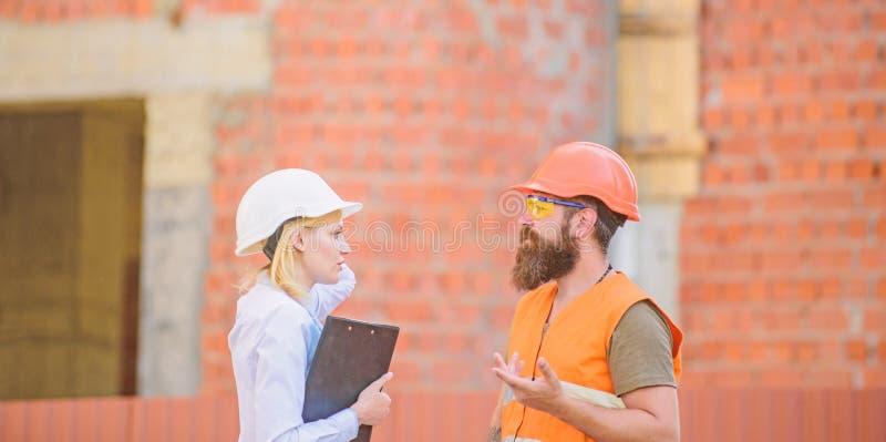 Het concept van de veiligheidsinspecteur De inspectie van de bouwwerfveiligheid Bespreek vooruitgangsproject Vrouweninspecteur en royalty-vrije stock afbeeldingen