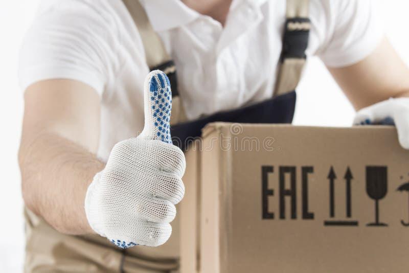 Het concept van de verhuizingsdiensten De lader in eenvormig toont duim op close-up Verhuizer met kartondoos De dragende bewegend stock afbeeldingen