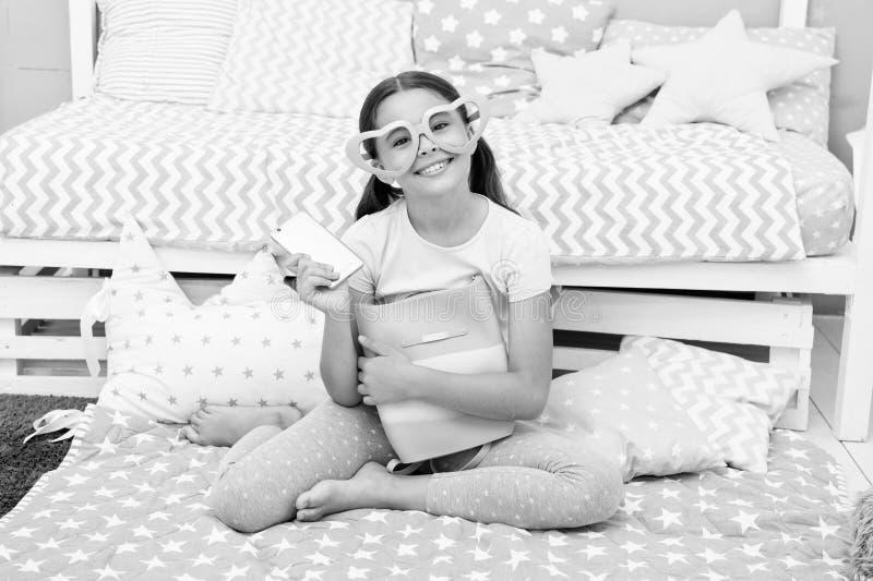Het concept van de verjaardag Het gelukkige gekregen meisje verjaardagsgeschenk Weinig kind in buitensporige glazen glimlacht met stock afbeelding