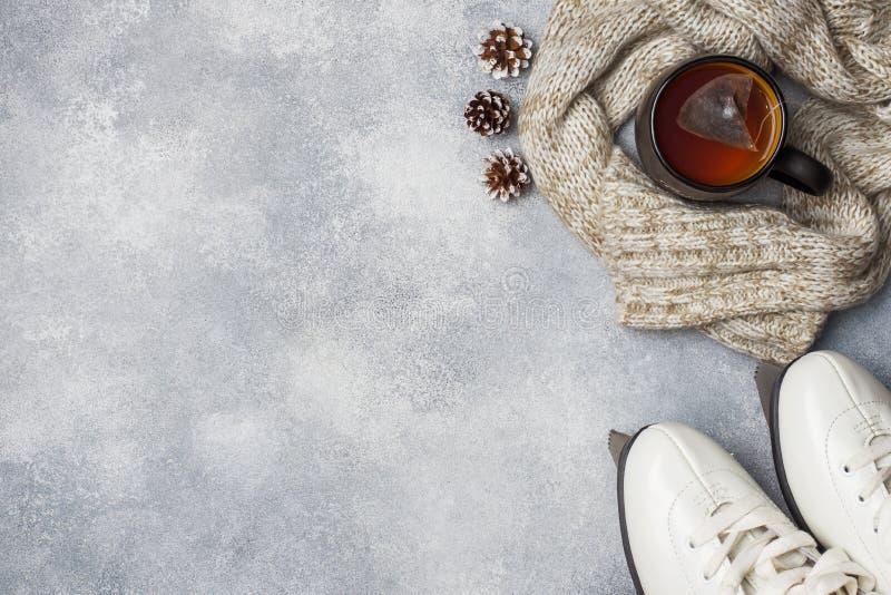 het concept van de de wintervakantie Schaatst warme kleren, Kop van hete thee met geurige kruiden op grijze achtergrond De ruimte stock afbeelding