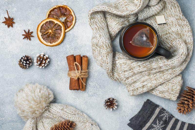 het concept van de de wintervakantie Warme kleren, Kop van hete thee met geurige kruiden op grijze achtergrond royalty-vrije stock foto