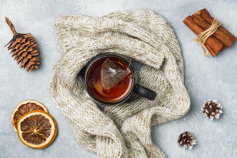het concept van de de wintervakantie Warme kleren, Kop van hete thee met geurige kruiden op grijze achtergrond stock foto's