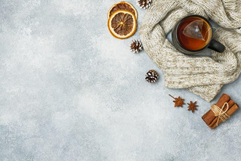 het concept van de de wintervakantie Warme kleren, Kop van hete thee met geurige kruiden op grijze achtergrond De ruimte van het  stock foto's