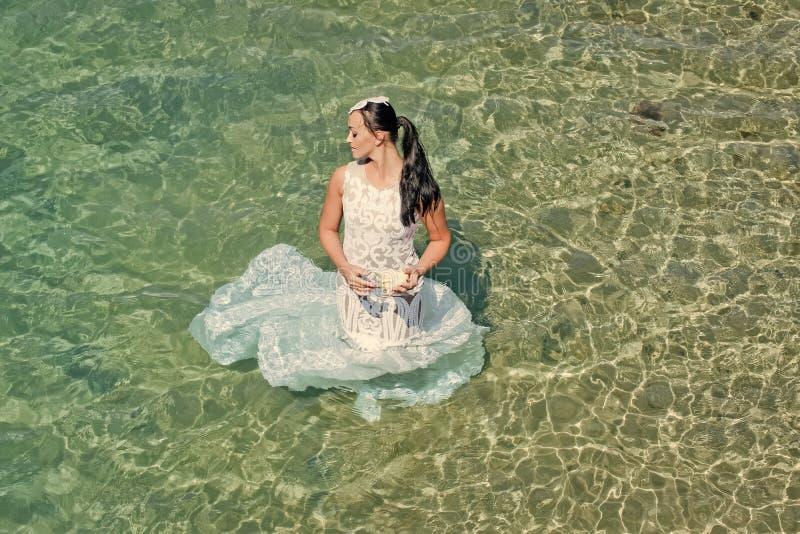 Het concept van de wittebroodswekenreis Manier en schoonheid Meisjeszitting in zeewater Bruid op zonnige de zomerdag op zeegezich stock foto