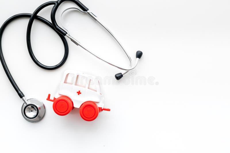 Het Concept van de ziekenwagendienst Het stuk speelgoed van het ziekenwagenvoertuig dichtbij stethoscoop op de witte ruimte van h royalty-vrije stock foto's