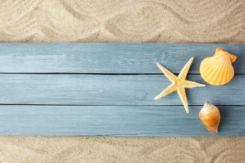 Het concept van de de zomertijd met overzeese shells en zeester op een blauw hout op zandachtergrond, exemplaarruimte royalty-vrije stock afbeeldingen