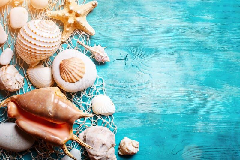 Het concept van de de zomertijd met zeeschelpen en zeester op blauwe houten raad Rust op het strand Achtergrond met exemplaarruim royalty-vrije stock foto