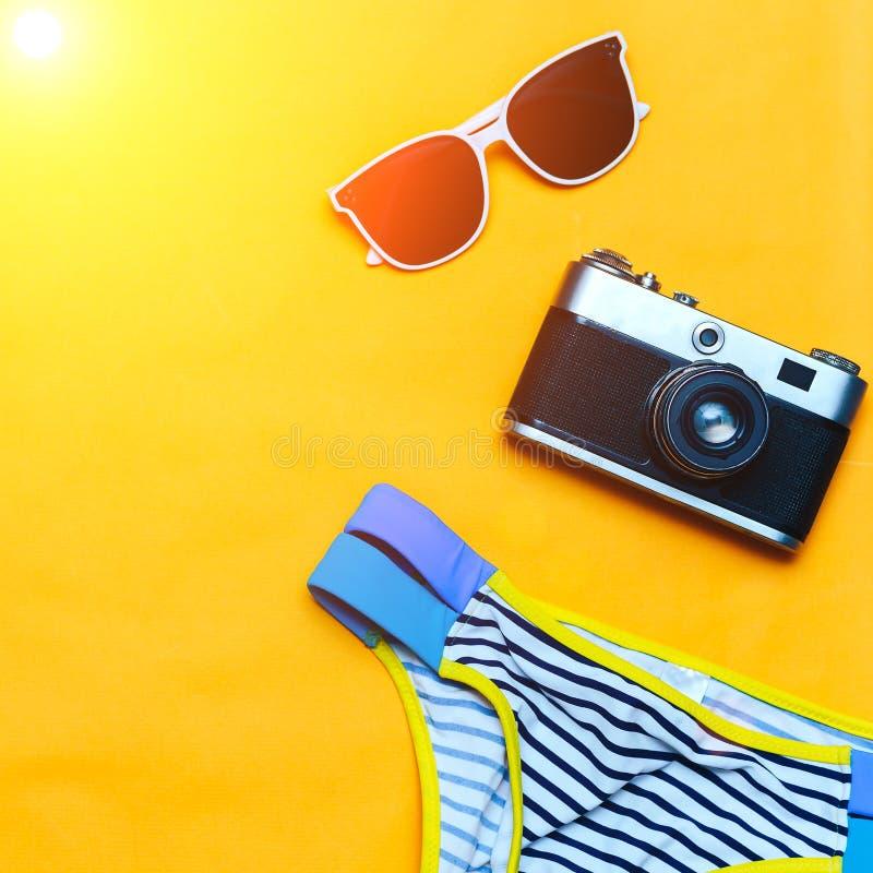 Het concept van de zomertoebehoren op gele achtergrond, flatlay, copyspace, uitstekende camera, wit zonnebril en zwempak royalty-vrije stock afbeelding