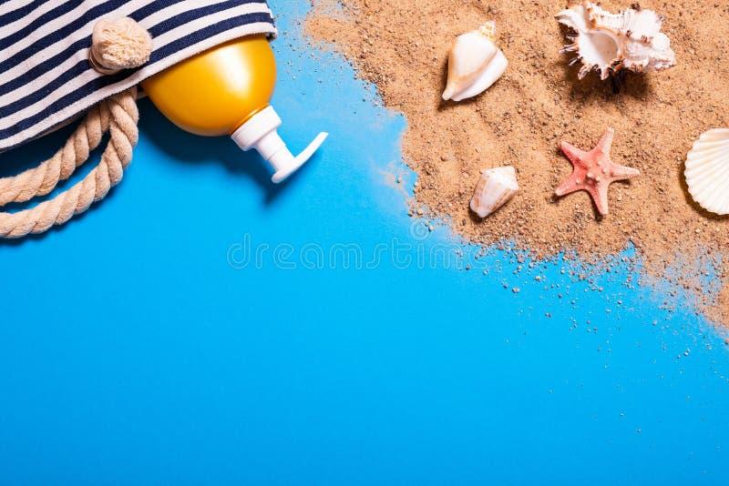Het concept van de de zomervakantie met zeeschelpen, zeester, het strandzak van vrouwen en zonnebrandoliefles op een blauw achter stock foto