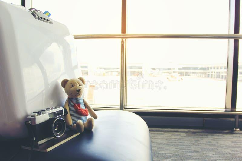 Het concept van de de zomervakantie, Teddybeer met paspoort en lege stoelen en passagier in de luchthaventerminal stock afbeeldingen