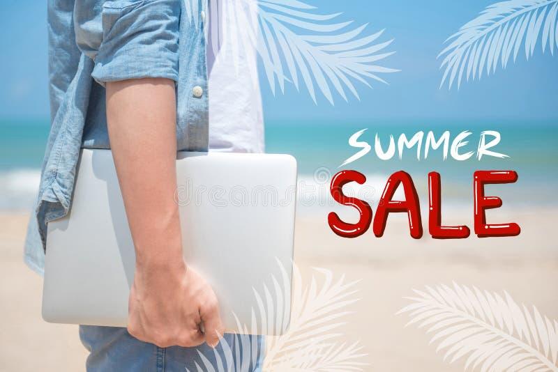 Het Concept van de de zomerverkoop Holdingslaptop op het strand royalty-vrije stock afbeeldingen