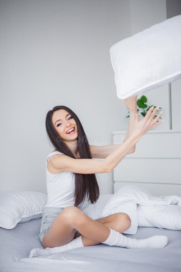 Het concept van de zorg Een mooie jonge glimlachende donkerbruine vrouw die in wit bed gelukzalig liggen comfortabel en royalty-vrije stock afbeeldingen