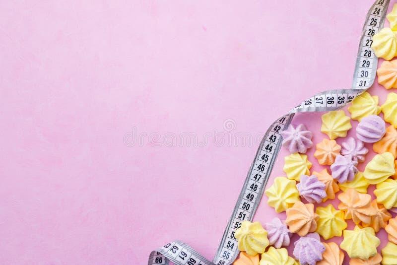 Het concept van het dieet schuimgebakjekoekjes en maatregelenband stock foto