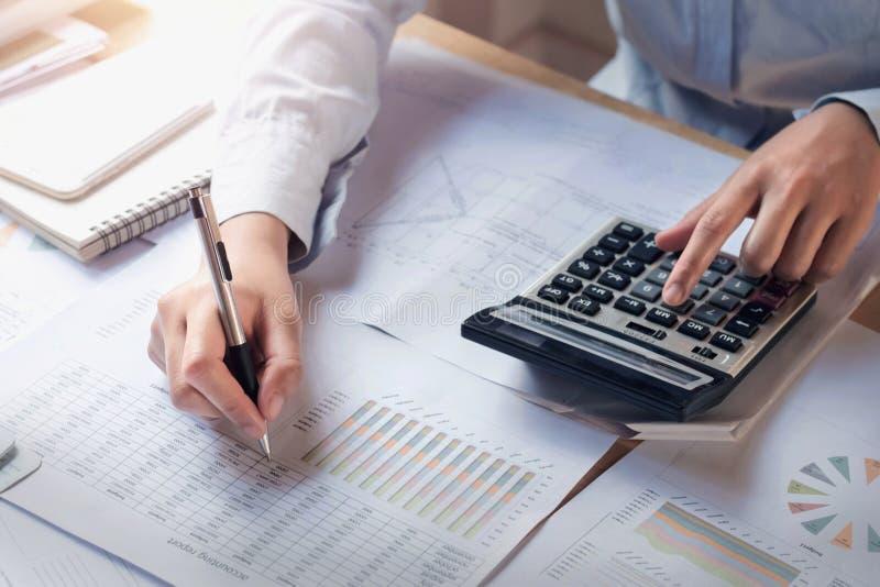 Het concept van financiën en van de boekhouding bedrijfsvrouw die aan bureau werken die calculator gebruiken om te berekenen royalty-vrije stock foto
