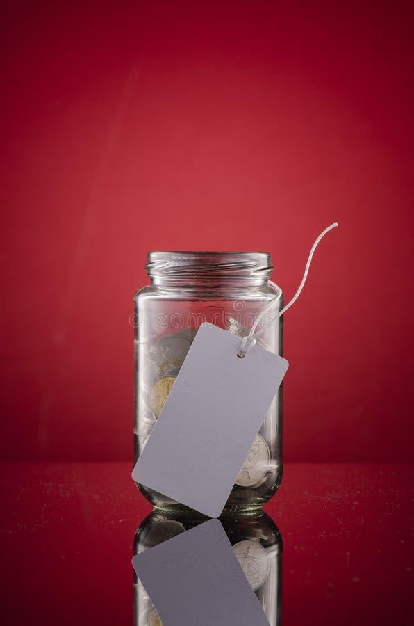 Het concept van geldbesparingen, het hoogtepunt van de glaskruik met muntstukken royalty-vrije stock fotografie