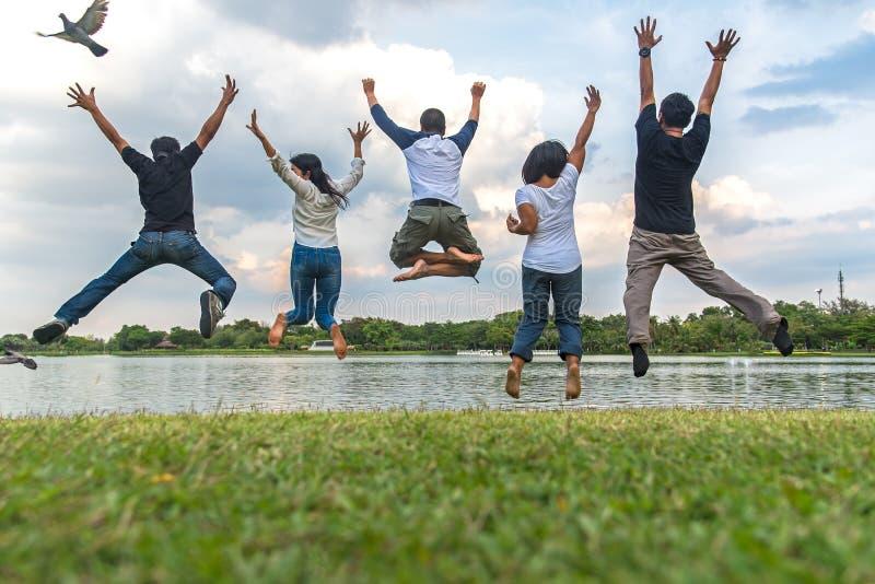 Het concept van het groepswerksucces met groep springende vrienden in het openbare park stock fotografie