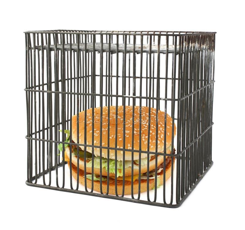 Het concept van het dieet - snel voedsel achter staven royalty-vrije stock afbeeldingen