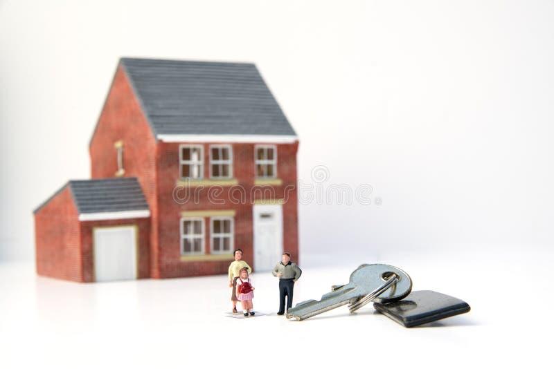Het concept van het familiehuis met modelhuis en mensen op witte backgro stock afbeelding