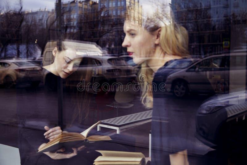 Het concept van het onderwijs Twee blondemeisjes zitten dichtbij venster in een bibliotheek royalty-vrije stock fotografie