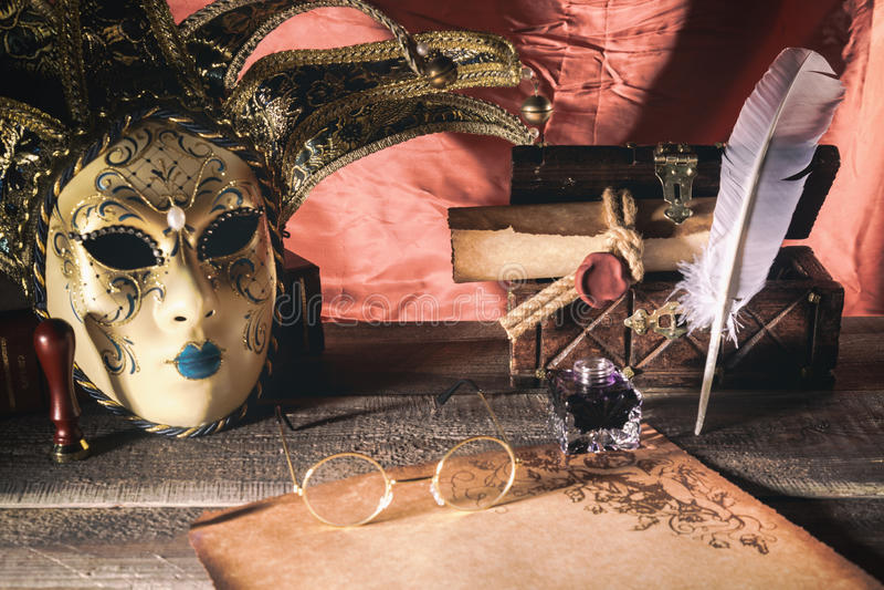 Het concept van het theater Uitstekend stilleven met schacht en rol dichtbij masker, oude borst en glazen op rode achtergrond royalty-vrije stock fotografie