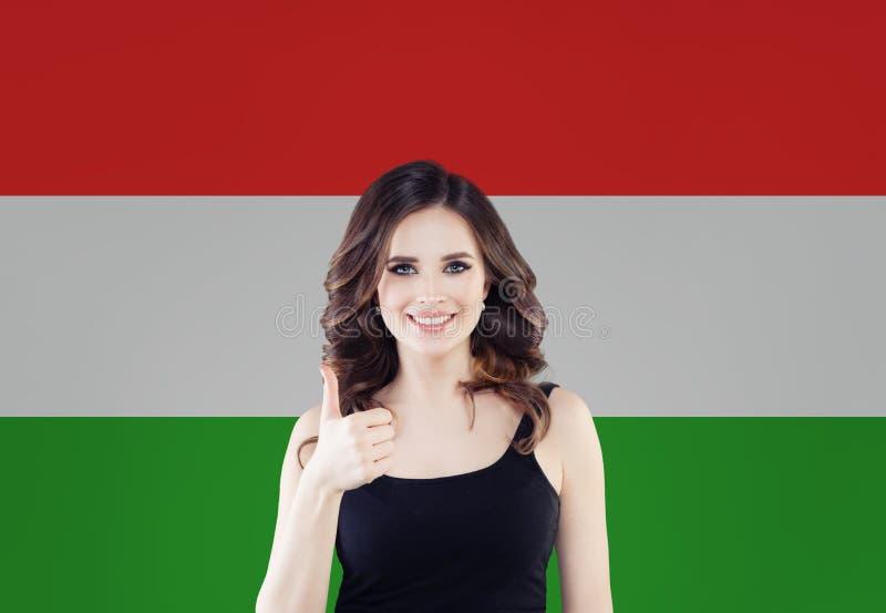 Het concept van Hongarije met mooie gelukkige vrouw met duim omhoog tegen de Hongaarse vlagachtergrond Reis in Hongarije royalty-vrije stock foto