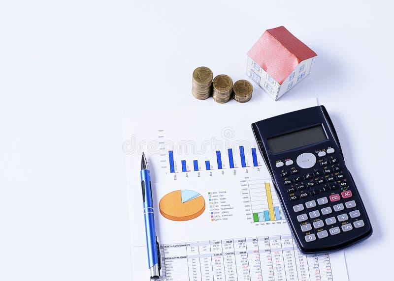 Het concept van hypotheekleningen met Huisdocument en muntstukkenstapel met pen en calculator op bedrijfsgrafiek royalty-vrije stock afbeelding