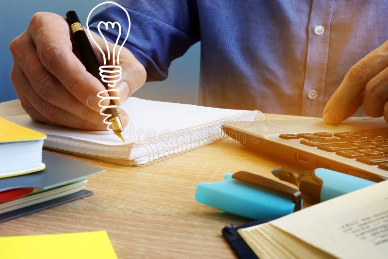 Het concept van ideeën Zakenman die in de nota en de gloeilamp schrijven Creatief proces royalty-vrije stock foto