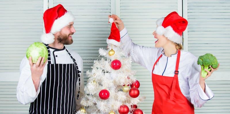 Het concept van het Kerstmisrecept Paar die gezonde maaltijd samen voor Kerstmisdiner voorbereiden Kokende Kerstmismaaltijd mens  stock afbeelding