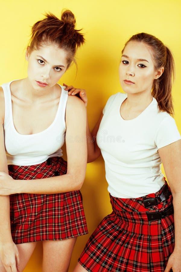 Het concept van levensstijlmensen: twee mooi schoolmeisje die pret op gele achtergrond, gelukkige glimlachende studenten hebben royalty-vrije stock foto's