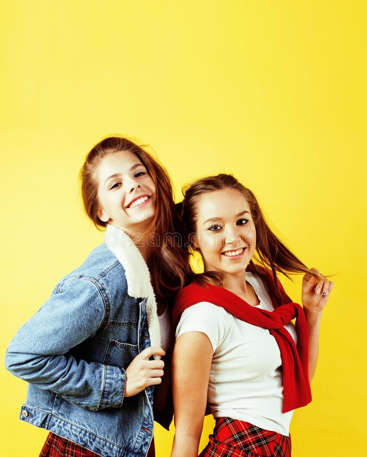 Het concept van levensstijlmensen: twee vrij jonge schooltieners die pret het gelukkige glimlachen op gele achtergrond hebben stock fotografie