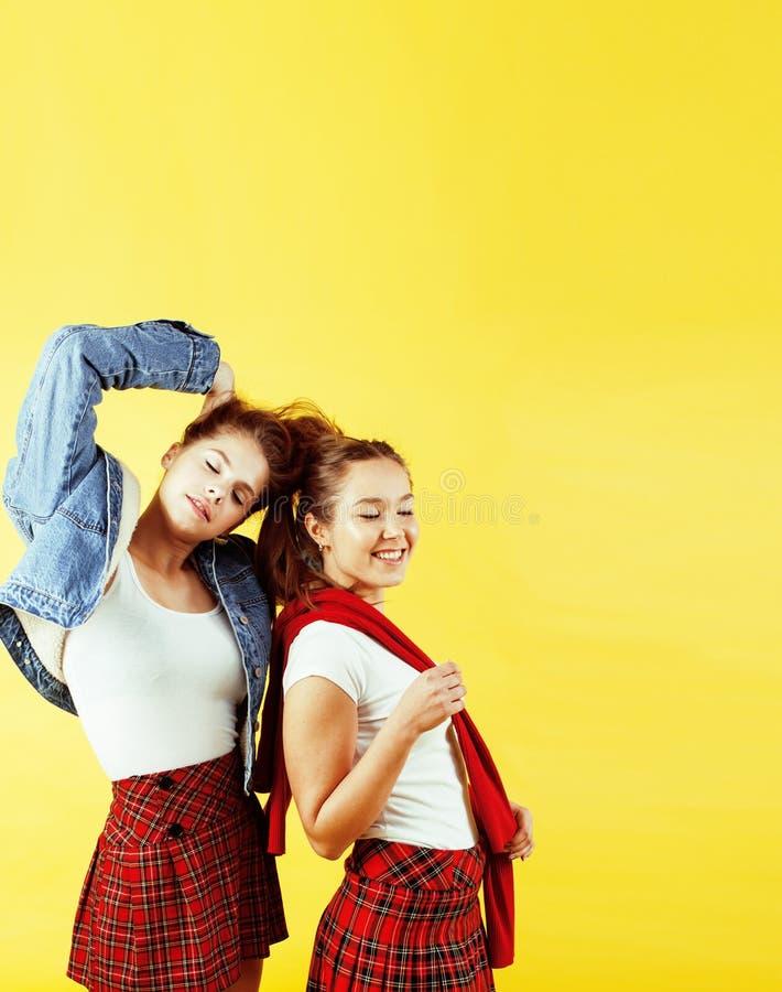 Het concept van levensstijlmensen: twee vrij jonge schooltieners die pret het gelukkige glimlachen op gele achtergrond hebben stock foto's