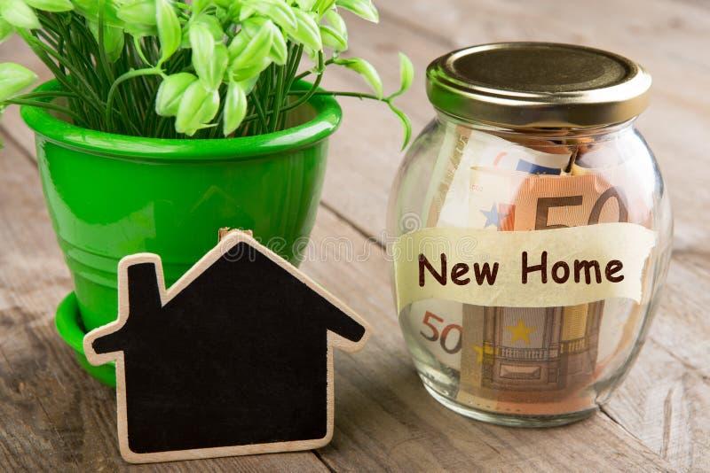 Het concept van onroerende goederenfinanciën - geldglas met Nieuw Huiswoord stock afbeeldingen