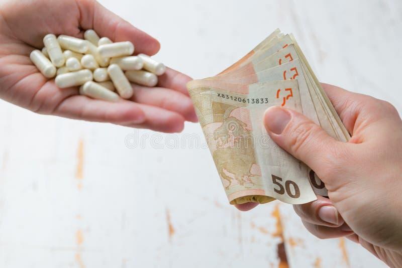 Het concept van Overpriceddrugs - handen die geld voor drugs ruilen Geneeskunde of verzekering verwant misdaadconcept stock afbeeldingen