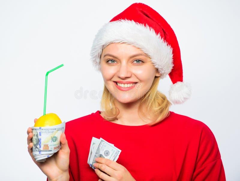 Het concept van het rijkdomsymbool Rijk meisje met citroen en geld De hoed van meisjessanta drinkt bankbiljet van de sap het citr stock afbeelding