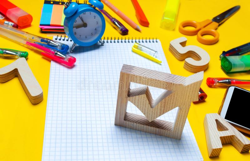 Het concept van schoolverkiezingen De doos en de schooltoebehoren van de verkiezingscontrole op een bureau op een gele achtergron royalty-vrije stock afbeelding