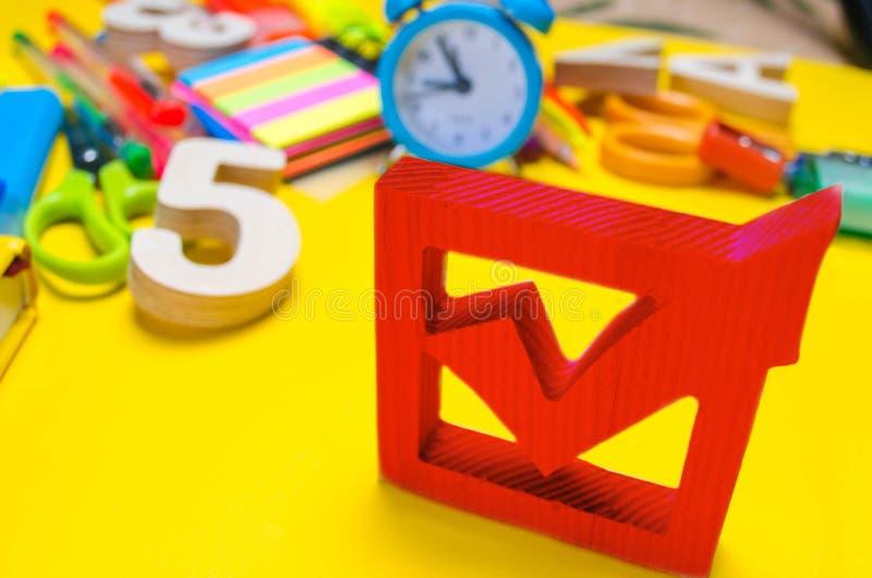 Het concept van schoolverkiezingen De doos en de schooltoebehoren van de verkiezingscontrole op een bureau op een gele achtergron stock fotografie