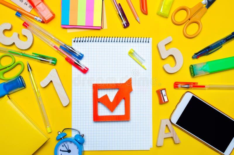 Het concept van schoolverkiezingen De doos en de schooltoebehoren van de verkiezingscontrole op een bureau op een gele achtergron stock foto