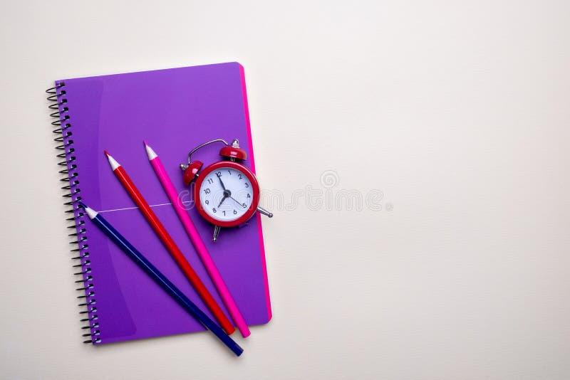 Het Concept van het tijdbeheer Rode uitstekende wekker, potloden en purpere blocnote stock afbeeldingen