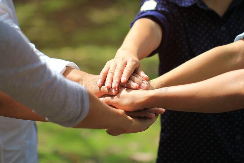 Het concept van het vergaderingsgroepswerk, Vriendschap, Groepsmensen met stapel handen die eenheid op natuurlijke groene achterg stock afbeeldingen