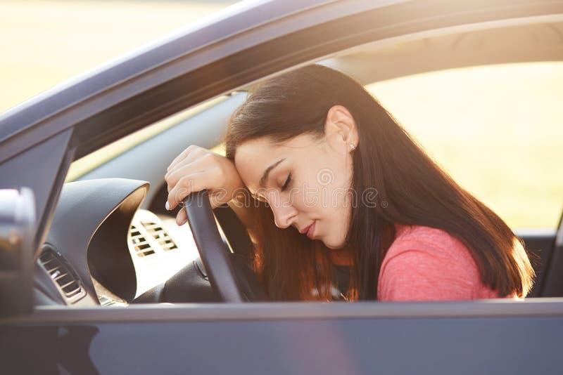 Het concept van het vervoer De vermoeide mooie vrouwenbestuurder heeft slaperige uitdrukking, wil het einde op weg zoals de aandr stock foto's