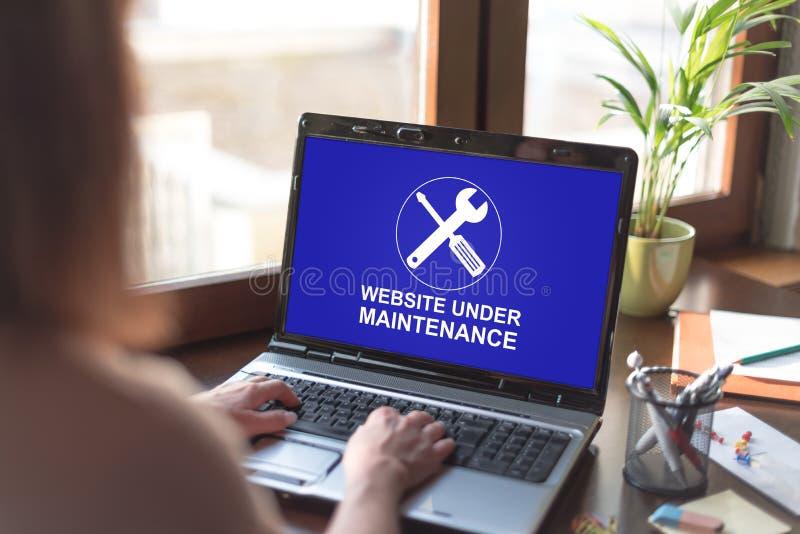 Het concept van het websiteonderhoud op het laptop scherm stock afbeeldingen