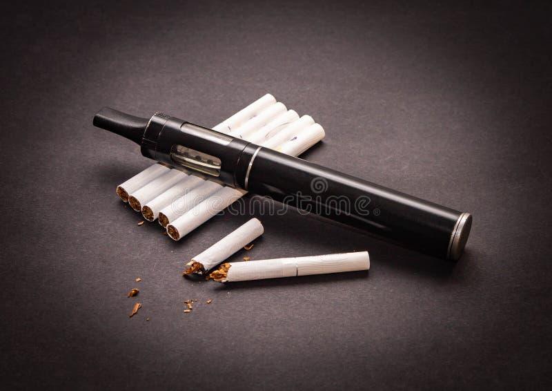 Het concept verstuiver tegen het roken is op de sigaret isoleert op donkere achtergrond stock afbeeldingen