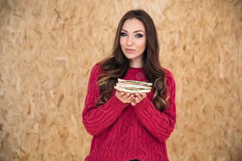 Het concept voeding, gezondheid en schoonheid Een jong mooi meisje met een vlotte huid houdt een sandwich met beide handen royalty-vrije stock foto