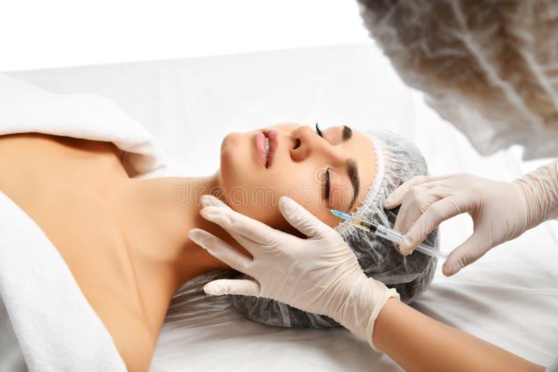 Het concepten dienen het jonge donkerbruine vrouw van de plastische chirurgieschoonheid gezicht en de arts handschoen met spuit i royalty-vrije stock foto