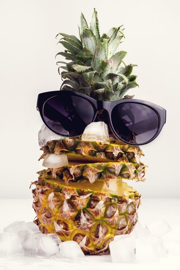 Het Concepten Verse Gesneden Ananas van het de zomervoedsel met Ijsblokje op Witte Ananas Als achtergrond en Gestemde Sunglass stock fotografie